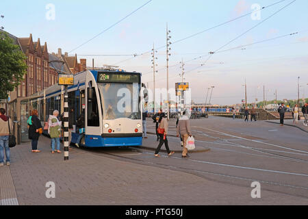 Tram stop near Central station in Amsterdam with people going in and coming off the tram - Stock Photo
