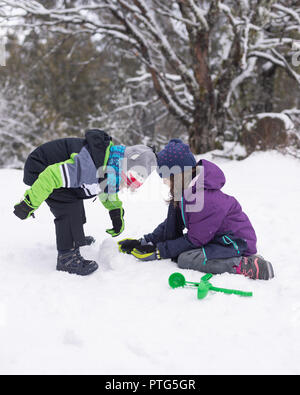 young boy and girl making snowballs - Stock Photo