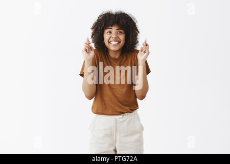 Indoor shot of charming dreamy optimistic dark-skinned female in brown t-shirt shrugging from impatience smiling broadly crossing fingers for good luck, waiting for dream come true over gray wall - Stock Photo