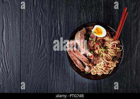 Soba noodles with sliced roasted beef, shiitake mushrooms, boiled eggs and fried vegetables in a bowl. Dark food photography. Top view - Stock Photo