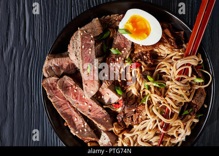 close-up of black bowl of Soba noodles with sliced roast beef, shiitake mushrooms, half of hard boiled egg and fried vegetables with chopsticks, asian - Stock Photo