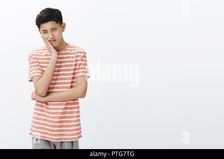 Portrait of lonely upset and bored young male asian student with dark short haircut leaning head on palm looking with gloomy indifferent look at camera watching boring movie to left side of copy space - Stock Photo