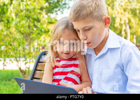 Smiling brother and sister sitting on bench in park and playing on laptop - Stock Photo