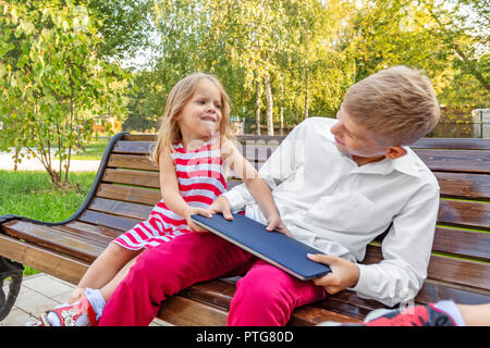 brother and sister in the park on a bench take away a laptop from each other - Stock Photo
