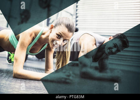 Muscular couple doing planking exercises - Stock Photo