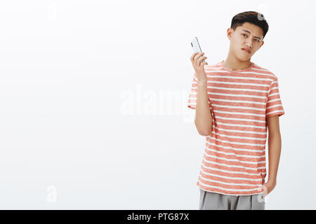 Bossy serious-looking cool young teenage asian guy in striped t-shirt taking away smartphone as being distracted. Guy turning away from cellphone not hear yell of mother as coming home late - Stock Photo