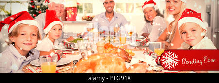 Composite image of happy family wearing santa hats around the dinner table - Stock Photo