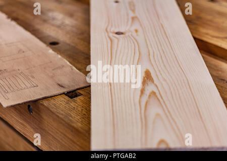 Eco-friendly woodworker's shop. Details and focus on the project sketches, sawdust, and planers or chisels, while making legs for a nut table. - Stock Photo