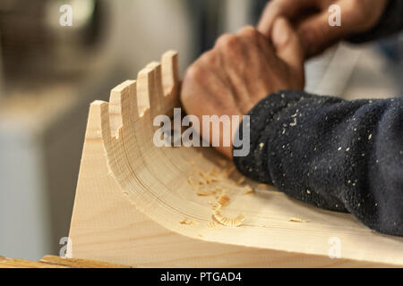 Eco-friendly woodworker's shop. Details and focus on the texture of the material, sawdust, and planers or chisels, while making legs for a nut desk. - Stock Photo