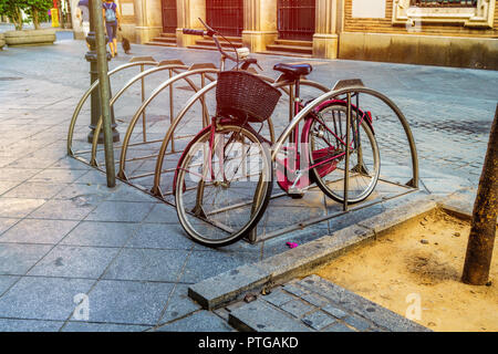 old bicycle parked on seville street - Stock Photo
