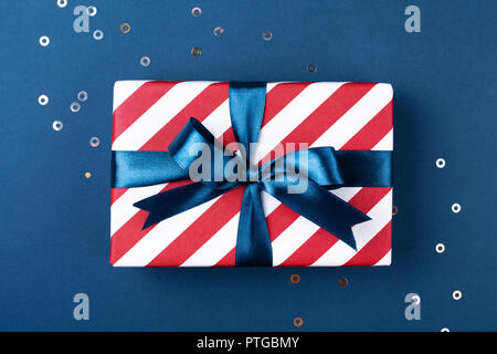 Gift box wrapped in red striped paper and tied with blue bow on blue background decorated with sparkles. Christmas card concept. - Stock Photo