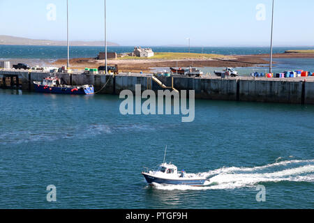 A speedboat in Stromness harbour in the Orkney. Beyond the jetty is the Inner Holm of Stromness, the Outer Holm is on the right - Stock Photo