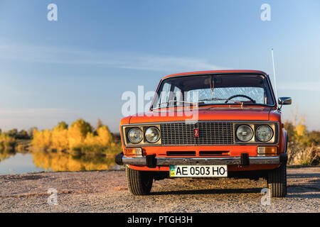 PERESHCHEPINO, UKRAINE - OCTOBER 12, 2014: Zhiguli VAZ 2106 original orange, released in the USSR in 70's. Car parked near the river, autuman time - Stock Photo