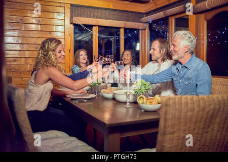 Friends toasting red wine glasses, enjoying dinner at cabin dining room table - Stock Photo