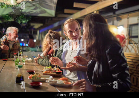 Couple eating, enjoying sushi on patio at night - Stock Photo