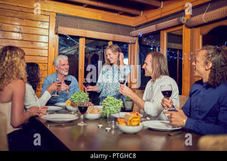 Friends celebrating, drinking red wine and enjoying dinner in cabin - Stock Photo