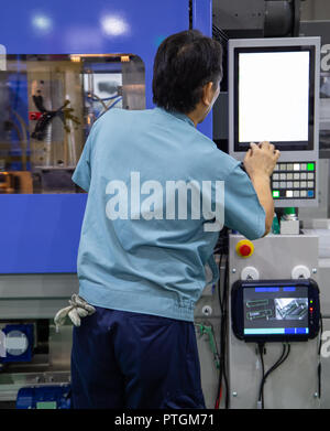 worker operate industrial plastic injection molding press machine for manufacturing - Stock Photo