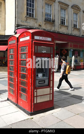 A red classic telephone box which has been converted to a cash ATM in Bath UK. 2018. - Stock Photo