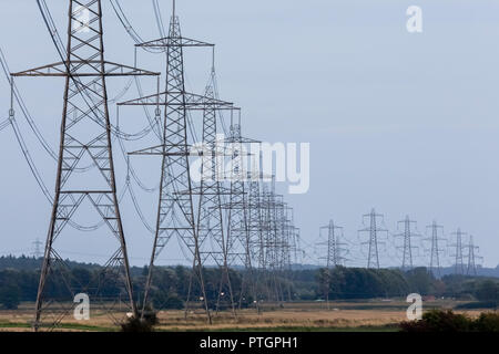 Electricity pylons or transmission towers carrying high voltage power lines and overhead cables above land as part of the national grid network supply - Stock Photo