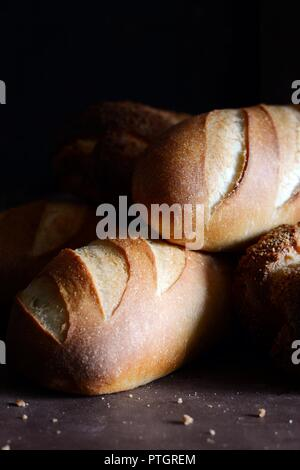 Delicious freshly baked bread on wooden background. Bakery product assortment with bread loaves, buns, rolls. Different kinds of bread - Stock Photo
