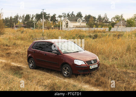 DNIPROPETROVSK REGION, UKRAINE - SEPTEMBER 18, 2016: Volkswagen Polo burgundy color parked on the dirt road in the autumn meadow near the countryside - Stock Photo