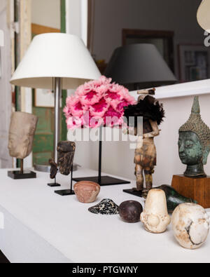 White plaster table with pink 1940's feather hat, Egyptian mace heads, native American Indian Kachina doll and a pre-Ankor Cambodian bust. - Stock Photo