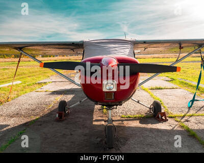 View of classic airplane on the grassy airfield; aircraft after the flight with cases on propellers and other elements; front view of small sport silv - Stock Photo