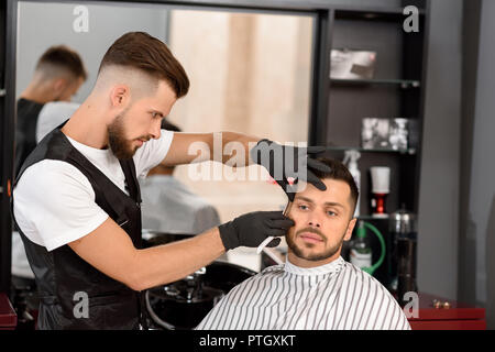 Confident barber concentrated on shaving man's beard using sharp razor. Handsome hairstylist wearing in white t shirt, black vest, and black gloves. Client covered with striped haircut gown. - Stock Photo
