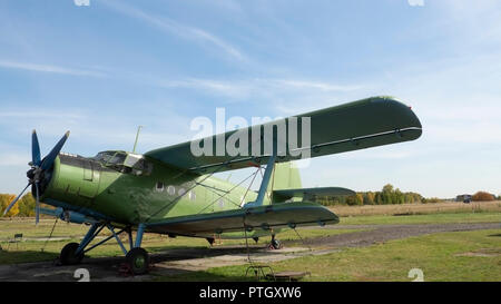 View of classic airplane on the grassy airfield; aircraft after the flight with cases on propellers and other elements; green military aircraft on the - Stock Photo