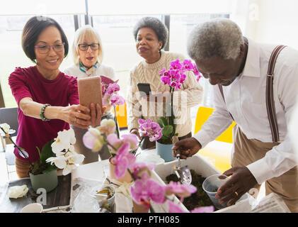 Active seniors enjoying flower arranging class - Stock Photo