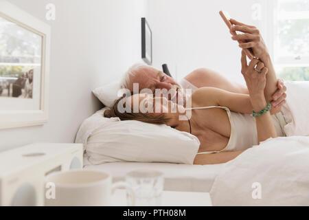 Affectionate senior couple using smart phone in bed - Stock Photo