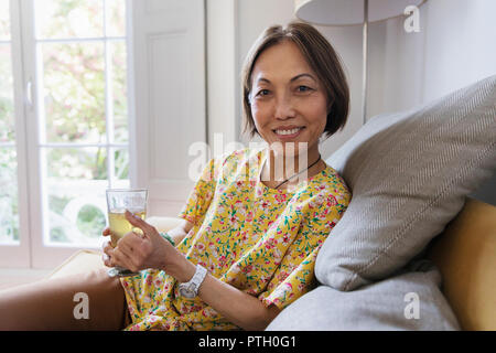 Portrait confident senior woman drinking tea in living room - Stock Photo