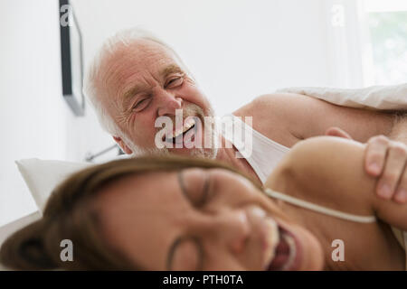 Playful, affectionate senior couple in bed - Stock Photo