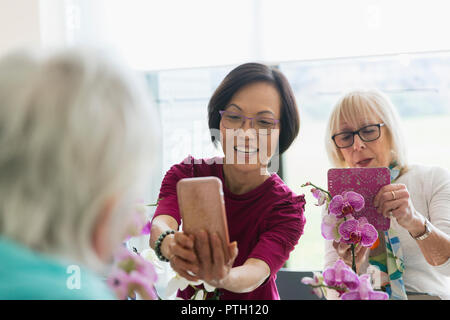 Active senior women with camera phone photographing orchids in flower arranging class - Stock Photo