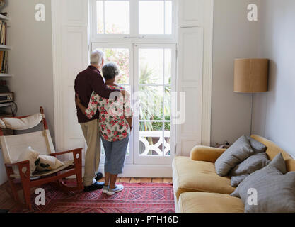 Affectionate, serene senior couple looking out living room window - Stock Photo