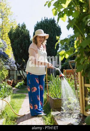Active senior woman gardening, watering plants - Stock Photo