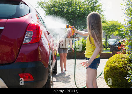 Mother and daughter washing car in sunny driveway - Stock Photo