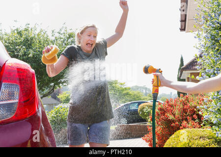 Daughter spraying mother washing car with hose - Stock Photo