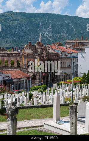 Mostar, Bosnia: the martyrs graveyard surrounded by buildings destroyed in the 1990s conflict in the cemetery nearby Nesuh-aga Vucijakovic Mosque - Stock Photo