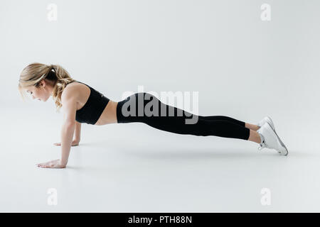 side view of young sportswoman doing push ups isolated on grey - Stock Photo