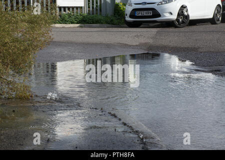 Burst water main leaking water onto road and pavement causing a flood - Stock Photo