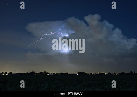 A lightningbolt strike into thin air as it jumps out of the top of a stormcloud - Stock Photo