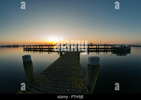 Sunset at River Rotte in Holland. Pier of a small harbor at river Rotte, close to Rotterdam. Sun is setting while the water is perfectly calm.