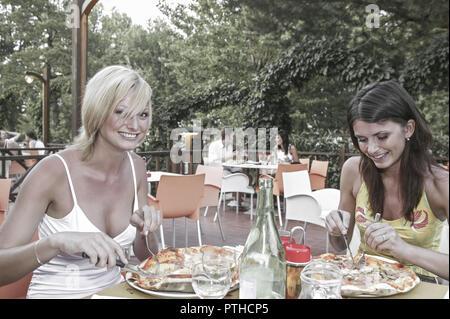 Frau Frauen Zwei Freundinnen Restaurant Garten Pizzeria Pizza Froehlich Halbportrait Aussen Lokal Jung Laecheln Stimmung Positiv Gluecklich Essen Spei - Stock Photo