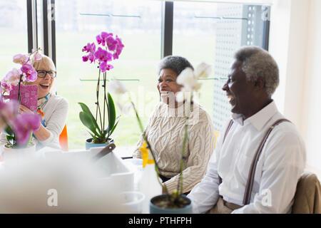 Happy active seniors enjoying flower arranging class - Stock Photo