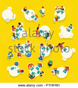 Overhead view of children eating lunch in school canteen - Stock Photo