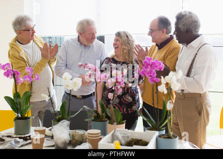 Active senior men clapping for female instructor in flower arranging class - Stock Photo