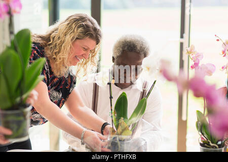 Female instructor helping active senior man in flower arranging class - Stock Photo