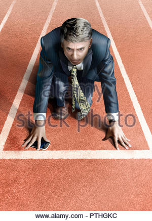 Businessman with money tie on starting line of athletics track - Stock Photo