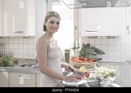 Kueche, kochen, Gemuese, schneiden, , probieren, 20-30 Jahre, Haushalt, Kuechenarbeit, Hausarbeit, Lebensmittel, Nahrungsmittel, vitaminreich, aufschn - Stock Photo